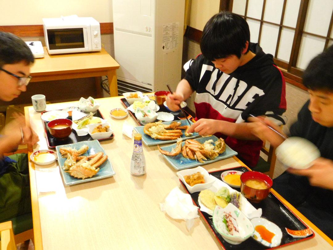 カニを食べる学生